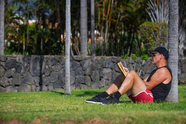 Atleet die een boek leest in het park
