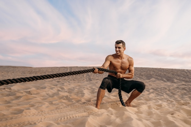 Atleet die oefening met slagtouwen in woestijn doet