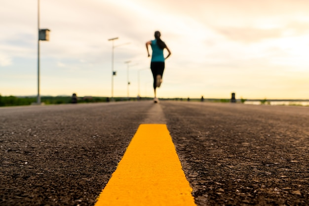 Atleet die op het wegpad loopt in zonsondergangtraining voor marathon en fitness.