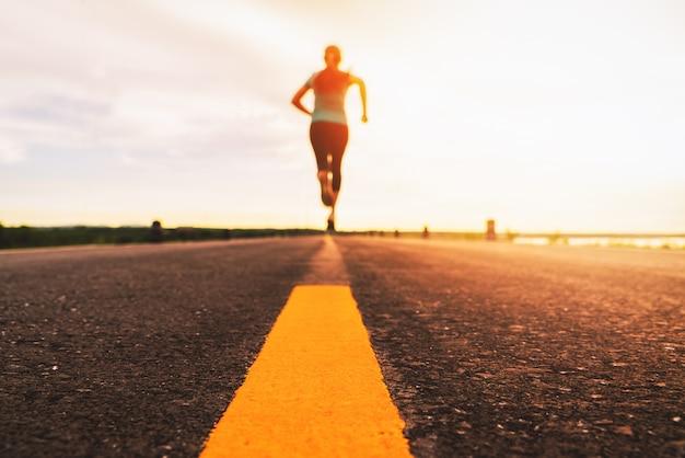 Atleet die op het wegspoor lopen in zonsondergang opleiding voor marathon en geschiktheid. bewegingsonscherpte van vrouw buitenshuis oefenen
