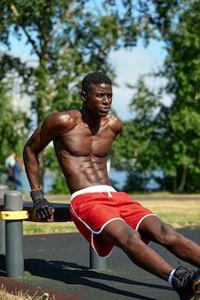 Atleet doet push-ups op het sportveld, afro-amerikaanse atleet doet push-ups op outdoor fitnessapparatuur, sportieve levensstijl, streven naar succes