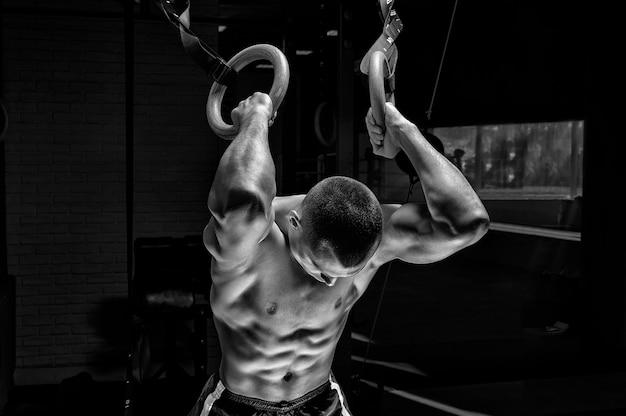 Atleet doet warming-up op gymnastiekringen. het concept van sport en een gezonde levensstijl. gemengde media
