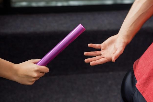 Atleet geeft een stokje door aan de partner