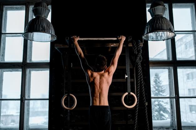 Atleet gespierde fitness mannelijk model omhoog te trekken op horizontale balk in een sportschool