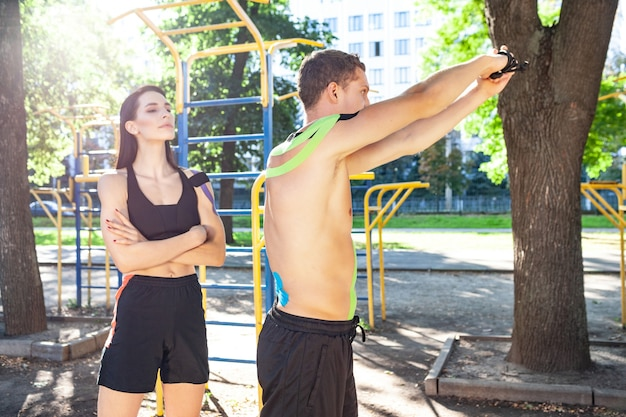 Atleet glimlachend brunette jonge vrouwelijke instructeur die knappe man helpt met korte broek met kinesiologie elastische tape op lichaamstraining armen met behulp van weerstandstouw op sportveld.