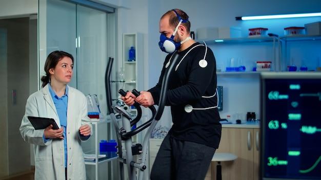 Atleet in gesprek met medisch onderzoeker die op crosstrainer loopt in een sportwetenschappelijk laboratorium dat vo2 max, hartslag, psychologische weerstand en spieruithoudingsvermogen meet