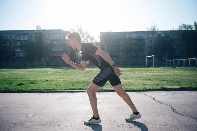 Atleet in het stadion staat op de startbaan voor hardlopen