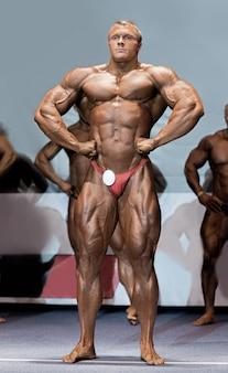 Atleet in lat spread pose. bodybuilder die spieren op het podium toont. een van de sterkste kanshebbers. kampioen worden.