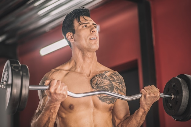 Atleet. jonge man met een tatoeage op een borst aan het werk met de halters in een sportschool