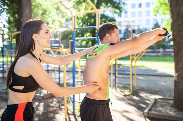 Atleet lachende brunette jonge vrouwelijke instructeur helpen knappe man met korte broek