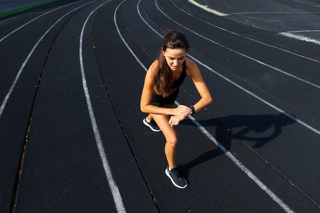 Atleet loper draait op atletische track haar cardio training. vrouw joggen voor competitie race zomer buiten stadion.