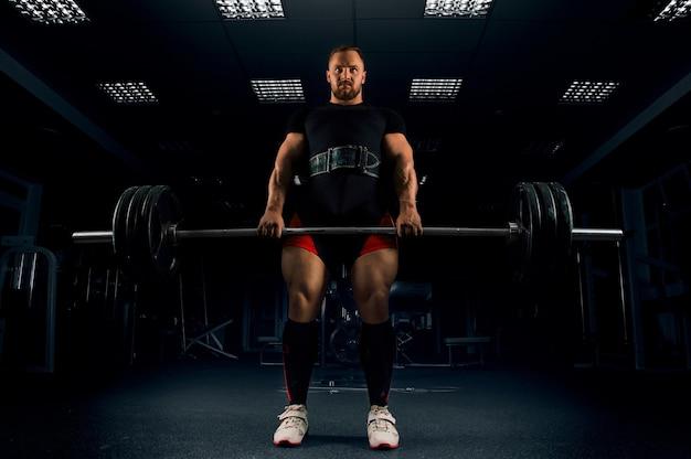 Atleet maakt een deadlift. hij heeft de balk bovenaan vastgemaakt en wacht op een telling