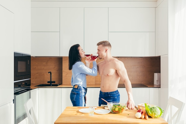 Atleet man bereidt lunch van groenten aan zijn vrouw, brengt samen vrije tijd door in de keuken