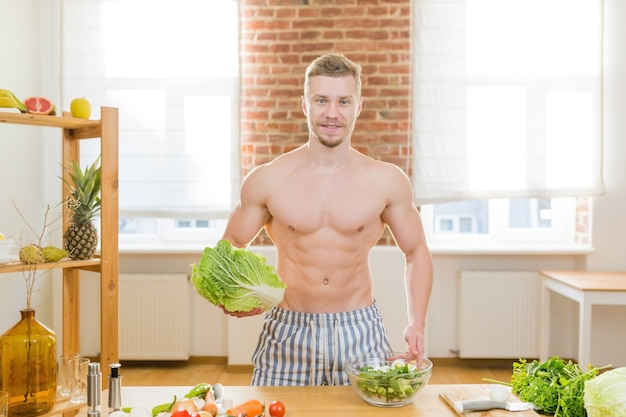Atleet man kookt in de keuken, gebruikt groenten en diverse soorten vlees voor het koken van het diner