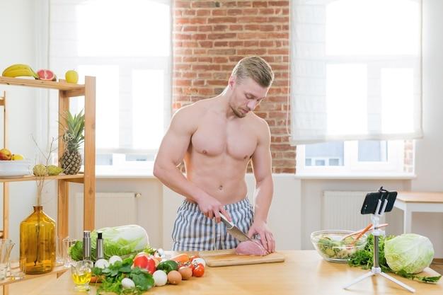 Atleet man kookt in de keuken, gebruikt groenten en verschillende soorten vlees om het avondeten te koken, kijkt naar online kookcursussen