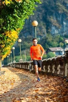 Atleet man loopt in de herfst tussen de bladeren