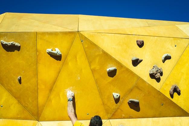 Atleet man probeert de top van een klimmuur te bereiken met de kracht van zijn handen en benen.