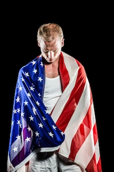 Atleet met amerikaanse vlag gewikkeld rond zijn lichaam