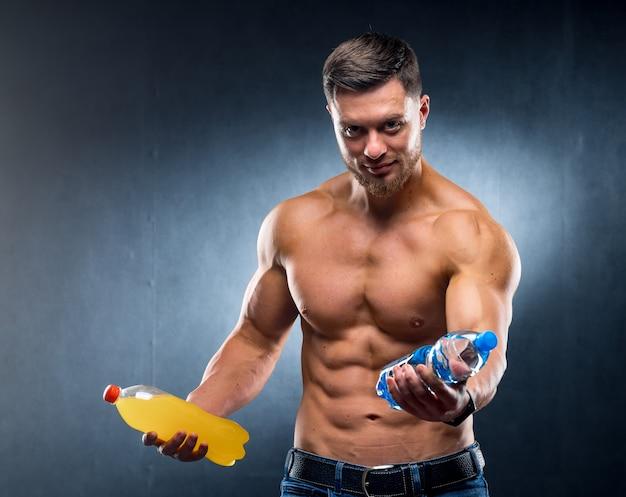 Atleet met een fles water en frisdrank. kiezen tussen gezonde en schadelijke drank. portret. detailopname