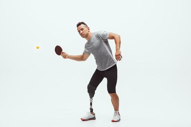 Atleet met een handicap of geamputeerde die op wit wordt geïsoleerd. professionele tennisser met beenprothese training