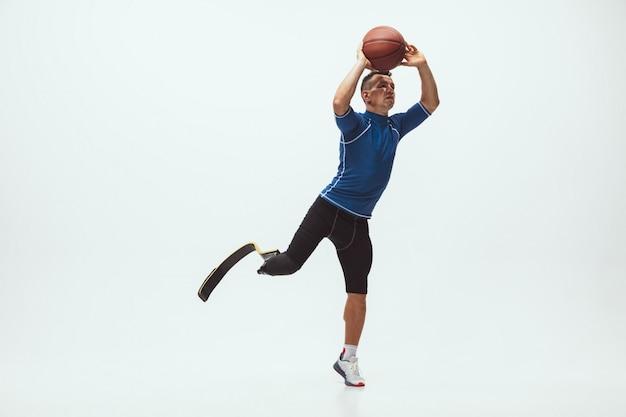 Atleet met een handicap of geamputeerde die op witte studioruimte wordt geïsoleerd. professionele mannelijke basketbalspeler met beenprothese die en in studio opleiden oefenen.