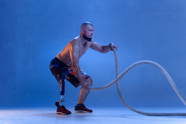 Atleet met een handicap of geamputeerde geïsoleerd op blauwe muur.