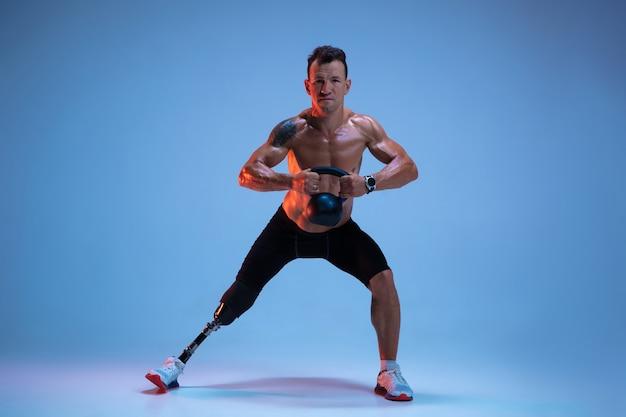 Atleet met een handicap of geamputeerde geïsoleerd op blauwe studio achtergrond. professionele mannelijke sportman met beenprothese training met gewichten in neon.