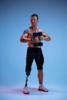 Atleet met een handicap of geamputeerde geïsoleerd op blauwe studio achtergrond