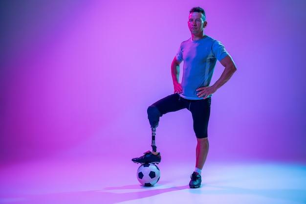 Atleet met een handicap of geamputeerde op de achtergrond van de gradiëntstudio in neon. basketballer