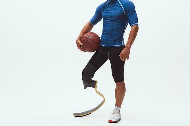 Atleet met een handicap of geamputeerde op witte studio achtergrond, basketbal
