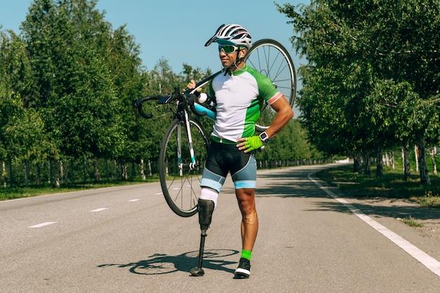 Atleet met een handicap of geamputeerde training in fietsen op zonnige zomerdag. professionele mannelijke sportman met beenprothese buiten oefenen. gehandicapte sport en gezonde levensstijl concept.