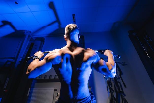 Atleet met een sterk lichaam die traint om de oefening in de sportschool omhoog te duwen. uitzicht vanaf de onderkant. blauwlichtfilter.