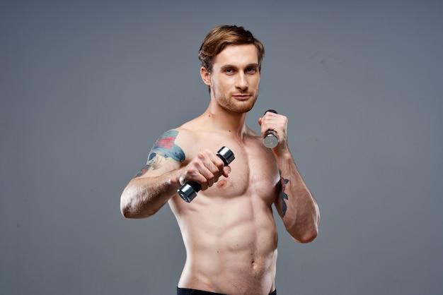 Atleet met een tatoeage en halters in handen telefoon fitness bodybuilding