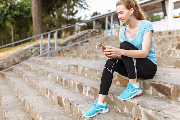 Atleet met een telefoon in haar handen, zittend op de trap
