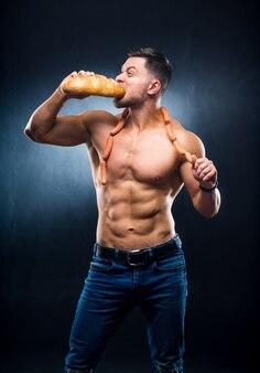 Atleet met naakte torso eet vers brood. worsten op een nek. bijgesneden foto. levensstijlconcept. studiofoto. hongerige sportman.