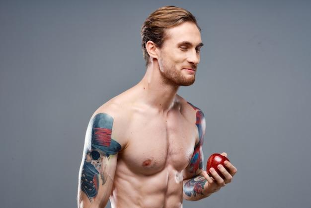 Atleet met opgepompte spieren eet een appel op een grijze achtergrond