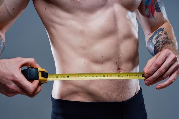 Atleet met opgepompte spieren meet zijn middel