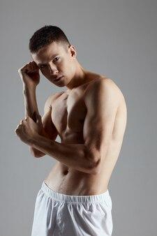 Atleet met opgepompte torso gebaren met handen op grijze achtergrond bijgesneden weergave