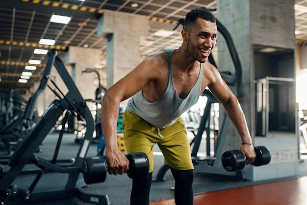 Atleet oefening met halters in de sportschool doet