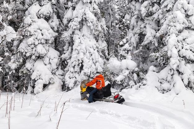 Atleet op een sneeuwscooter die zich in het winterbos beweegt