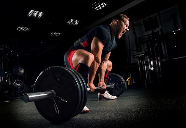 Atleet schreeuwt in de sportschool om zichzelf te motiveren om een oefening genaamd deadlift uit te voeren