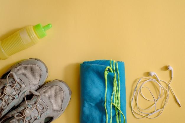 Atleet set met vrouwelijke kleding, halters en fles water op geel