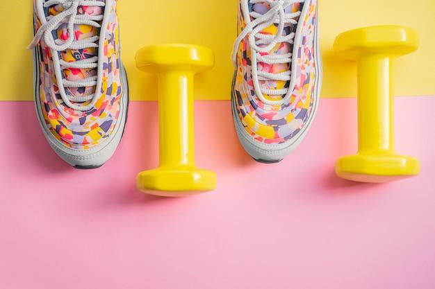 Atleet set met vrouwelijke lopende sneakers en halters geel-roze achtergrond. fitness concept. apparatuur voor gym en thuis