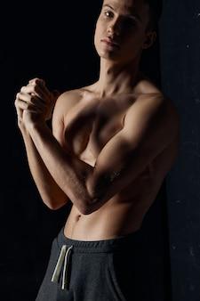Atleet sloeg de handen ineen op zwarte achtergrond fitness biceps spieren model bijgesneden weergave