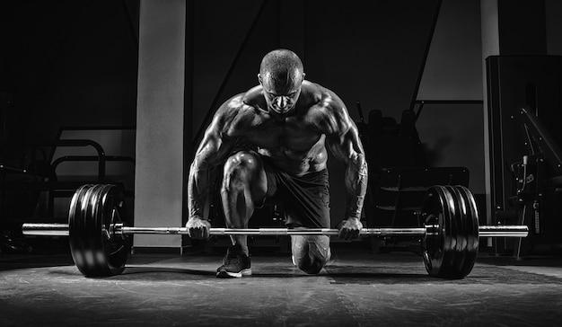 Atleet staat op zijn knie en in de buurt van de bar in de sportschool en bereidt zich voor op een deadlift. gemengde media