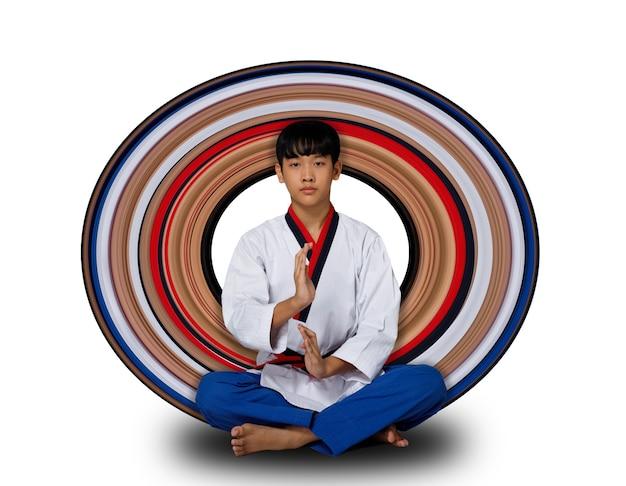 Atleet tienerjongen zit meditatie als zen-krijger voordat hij gaat vechten. 12 jaar oude sportman klaar zijn geest en kalme stemming over witte achtergrond geïsoleerd volledige lengte