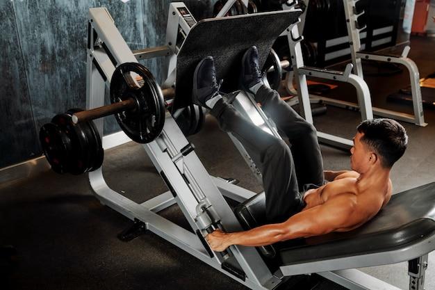 Atleet training op beenpers machine