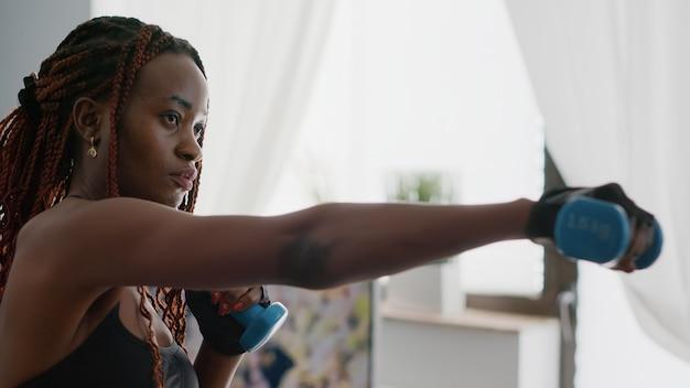 Atleet zwarte vrouw die sportkleding draagt die aërobe training beoefent