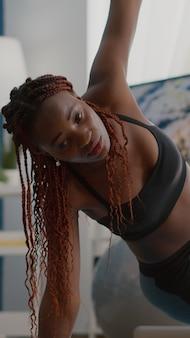 Atleet zwarte vrouw training op yoga kaart in woonkamer staande in zijplank