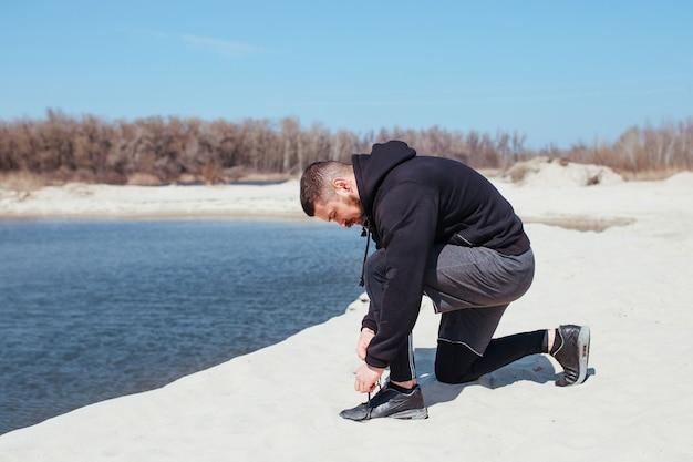 Atleetloper die schoenveters strikt voordat hij buiten gaat trainen